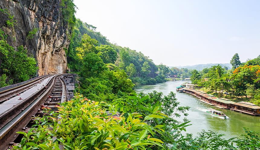 Sulla sinistra una ferrovia e sulla destra, in basso, un fiume che scorre tra vegetazione tropicale