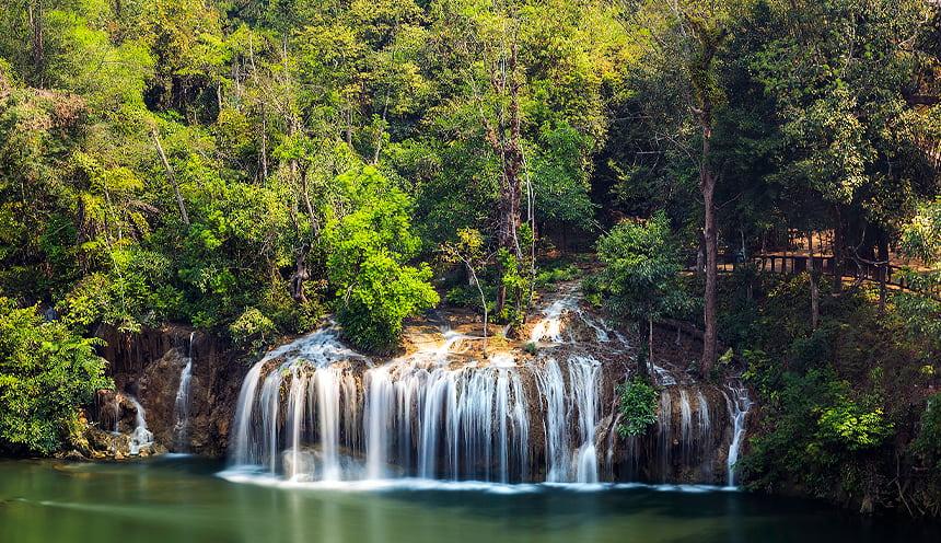 Foto di una cascata abbastanza larga circondata da vegetazione e alberi tropicali