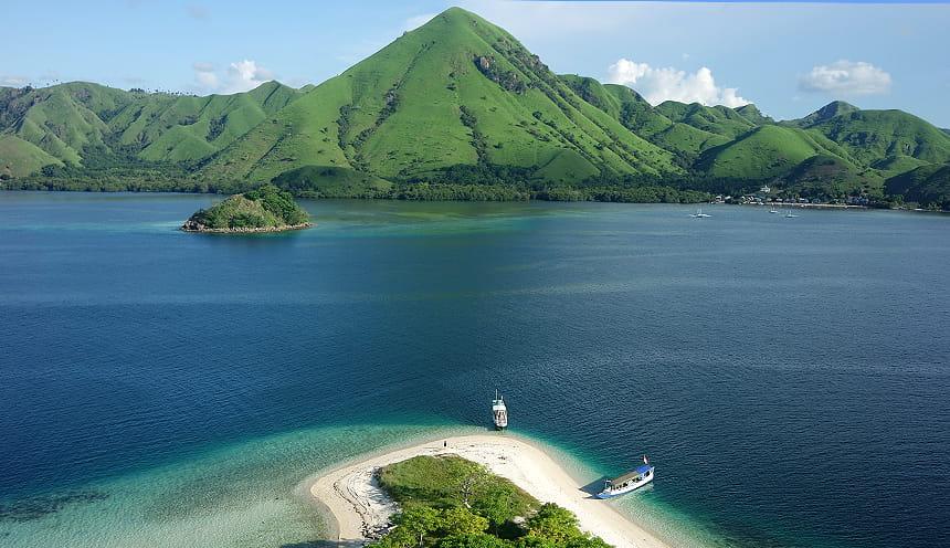 Panoramica con in fondo un'isola con al centro una montagna a piramide. Al centro il mare e in basso una piccola spiaggia.