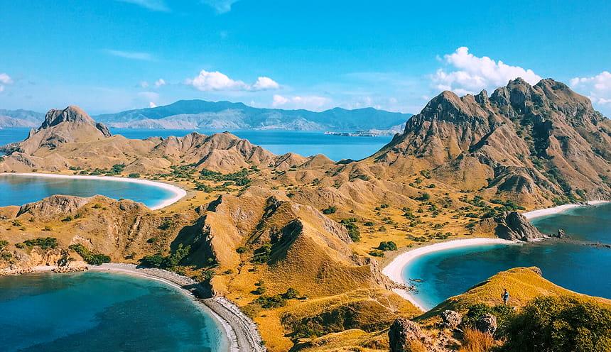 Panoramica di un isola che si apre davanti in due baie a destra e sinistra. Sulla baia di destra svettano alture semi-rocciose.