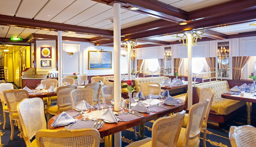 La sala da pranzo del veliero con diverse tavoli apparecchiati.