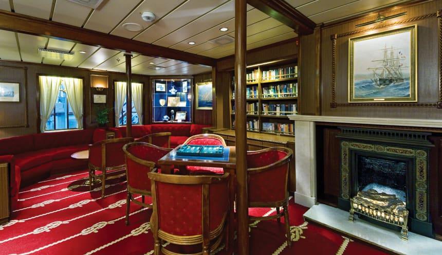 Una sala interna di un veliero, con quadri, una libreria e un tavolino su un pavimento rosso soffice.