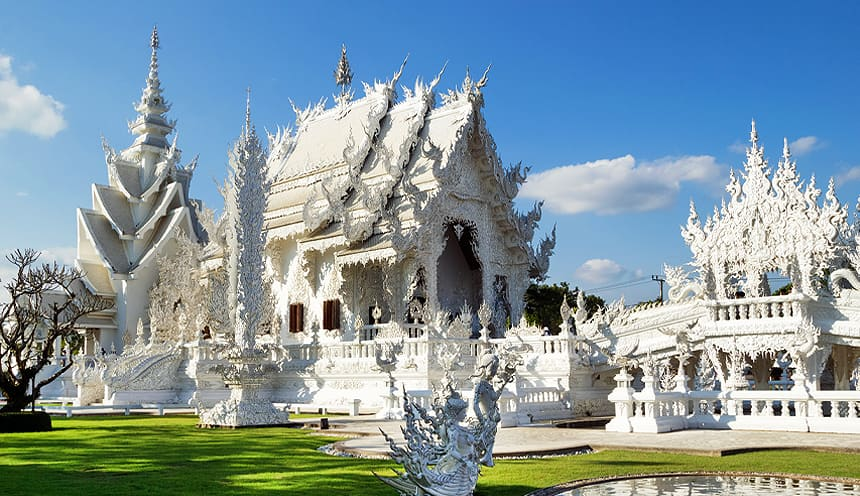 Un tempio buddhista bianco e ricco di dettagli e sculture.