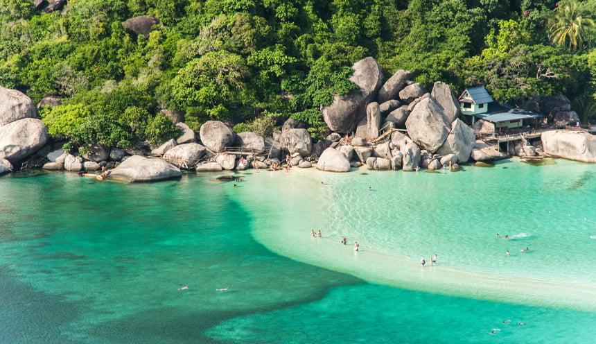 In primo piano il mare di color smeraldo attraversato da una sottile linea di sabbia centrale e sullo sfondo la costa tropicale di una delle isole di Koh Nang Yuan