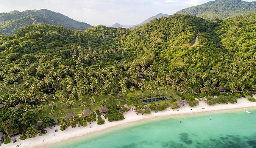 Da destra a sinistra si allunga una spiaggia bianca e alle sue spalle palme e vegetazione