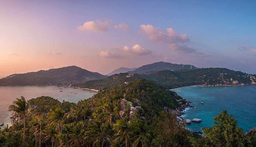 Al centro una penisola con un verde promontorio bagnato a destra e sinistra dal mare, durante il tramonto.