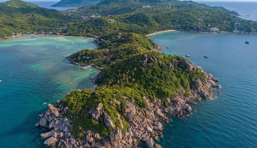 in primo piano un promontorio ricoperto da vegetazione e circondato dalle acque blu del mare in fondo a destra e sinistra si aprono due spiagge