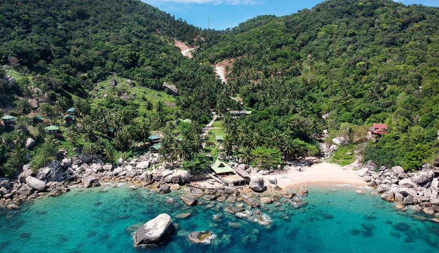 In primo piano le acque turchesi bagnano una spiaggia sabbiosa sulla destra e un gruppo di scogli sulla sinistra. Dietro vegetazione tropicale.