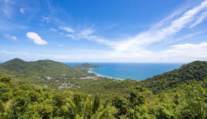 Vista panoramica con in lontananza baia ampia bagnata da acque smeraldine e immersa nel verde acceso e fitto della foresta tropicale