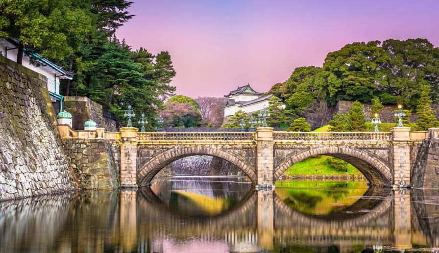 Un ponte in pietra e alle spalle la parte superiore di un castello in stile giapponese.