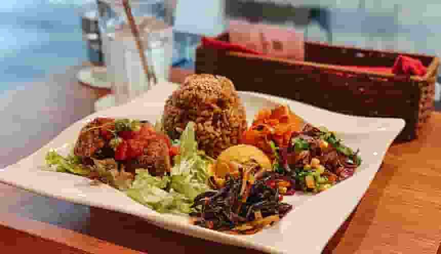 Un piatto con del riso, verdura e diversi altri ingredienti.