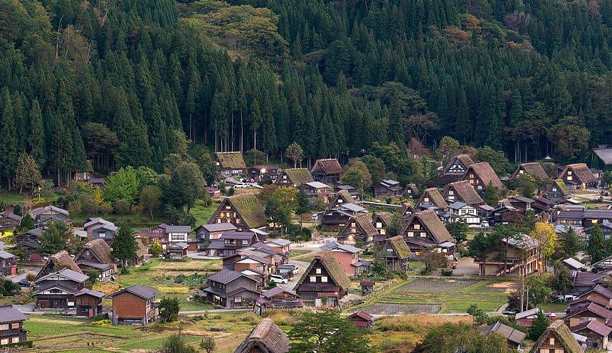 Un villaggio di case dai tetti di paglia a spiovente circondate da boschi.