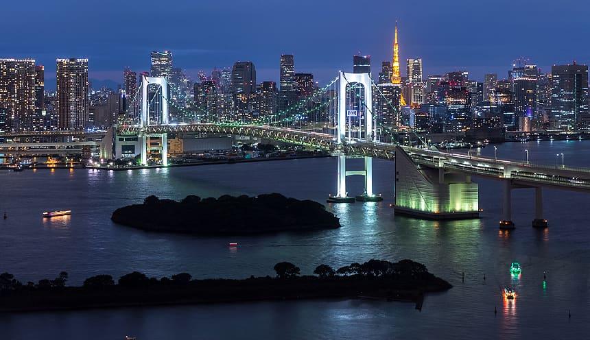 Lo skyline serale di Tokyo con un lungo ponte in primo piano.