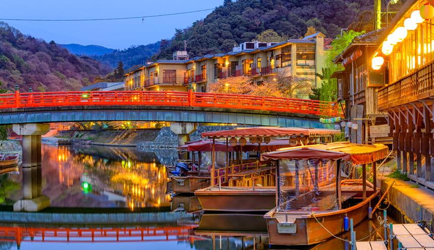 Un ponte rosso e alcune barche a riva.