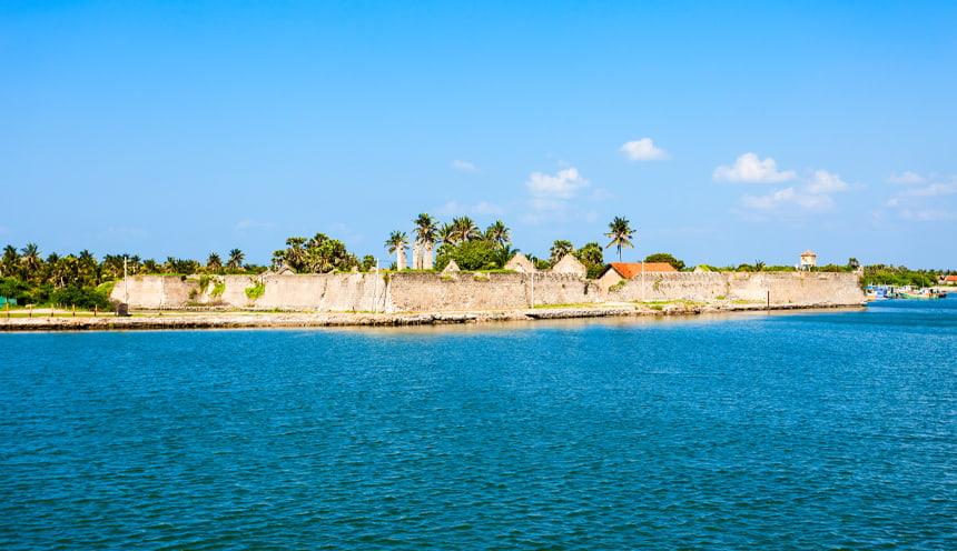 Al centro le mura di un forte coloniale con alcune palme alle spalle. In primo piano il mare azzurro.