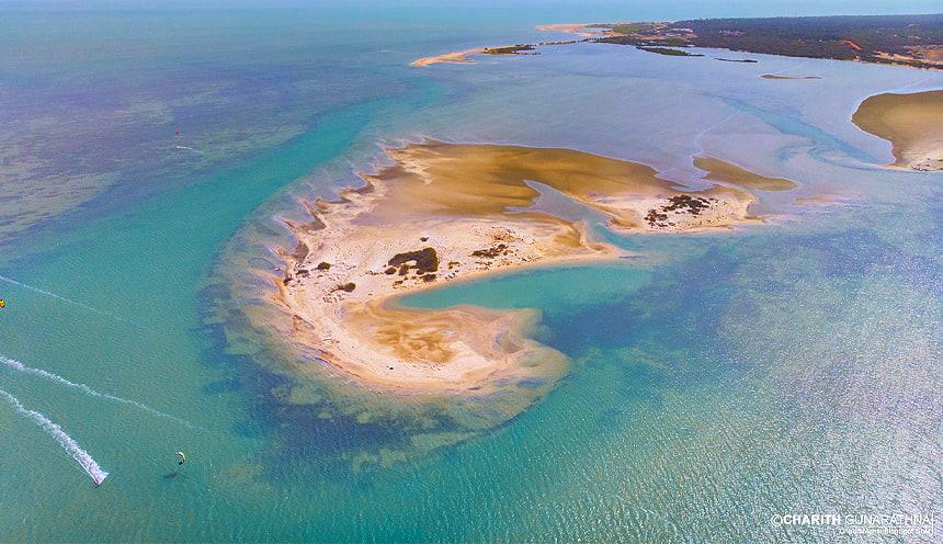 Foto aerea di una piccola isola sabbiosa color giallo-ocra, circondata da acque smeraldine e da due kite-surf