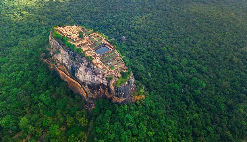 Immersa nel verde di alberi una roccia si erge con sulla sommità i resti di un antico palazzo con una piscina artificiale.