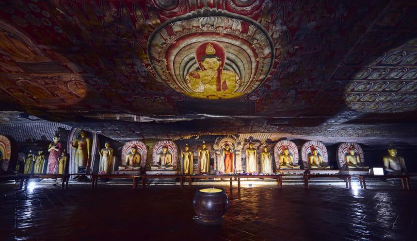 Una grotta finemente decorata da affreschi raffiguranti un grosso cerchio con al centro il Buddha. Sul fondo diverse statue del Buddha.