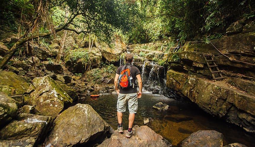 Un escursionista si affaccia su un lago e una cascata, circondato da vegetazione tropicale del parco nazionale di Bach Ma.
