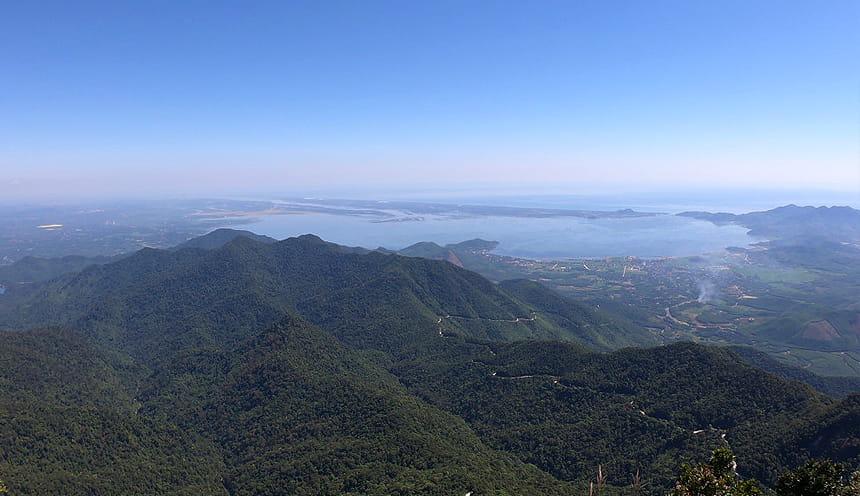 Foto panoramica di una catena montuosa verde bagnata a nord dalle acque del mare e una strada sinuosa che dalla montagna porta al mare.
