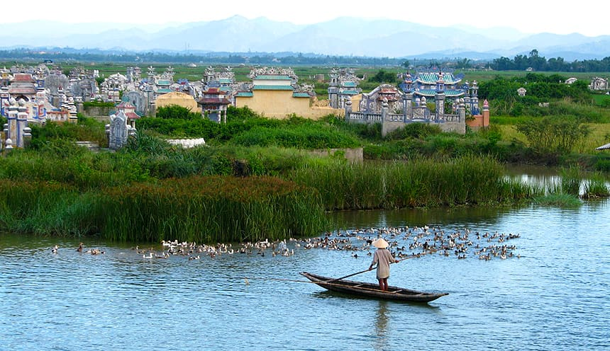 Una canoa con a bordo un uomo in piedi con un remo. In fondo la sponda del fiume con diverse tombe.
