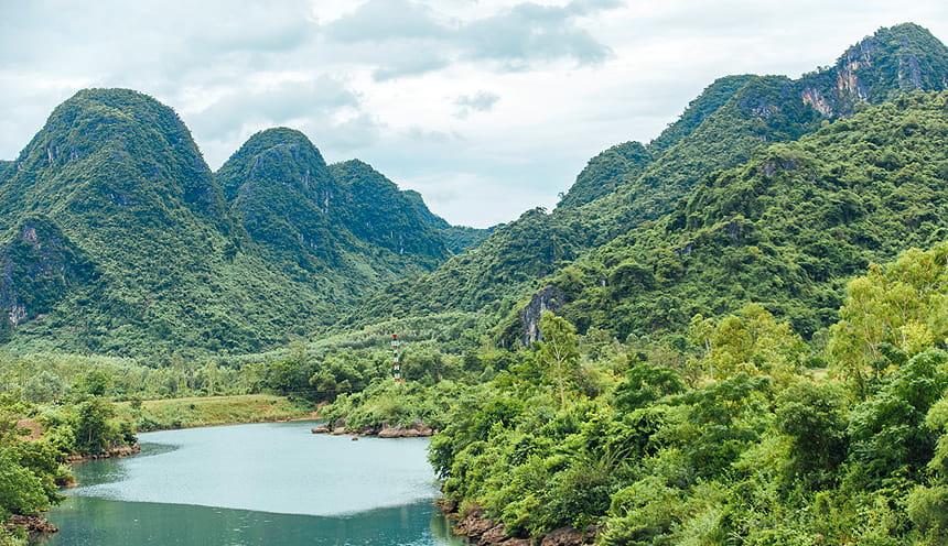 Panoramica di una valle circondata in fondo da picchi verdeggianti e al centro un lago.