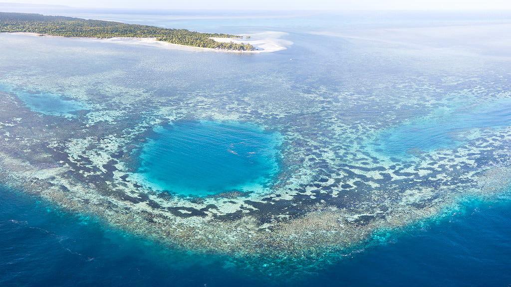 Vista aerea di una laguna di Wakatobi con barriera corallina a sfioro sulle acque turchesi