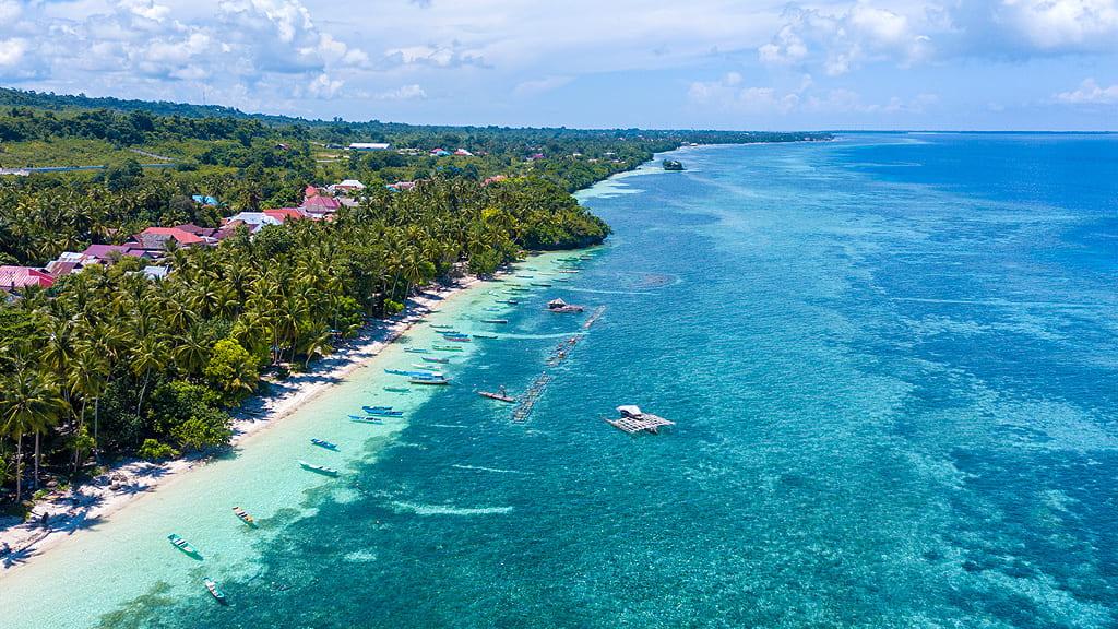 Vista aerea di una spiaggia di Wakatobi, acque turchesi, barche e il verde di palme e vegetazione tropicale sulla sinistra
