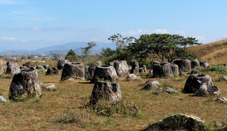 Diverse giare in pietra senza coperchi, su un prato ingiallito. Particolare del sito numero 1 della Piana delle Giare.