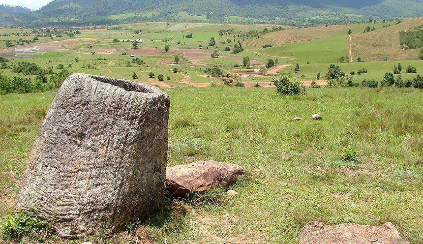 Sulla sinistra una giara in pietra in primo piano si affaccia su una vallata verde con qualche albero e campo coltivato.