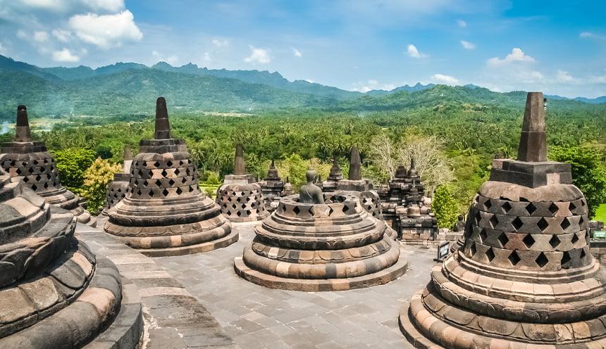 Vista da uno degli ultimi livelli del templio con diverse stupa in primo piano e la foresta sullo sfondo