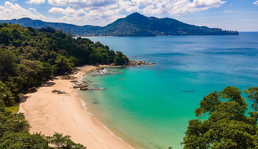 Foto di una spiaggia tropicale sulla sinistra e acque color smeraldo sulla detra.