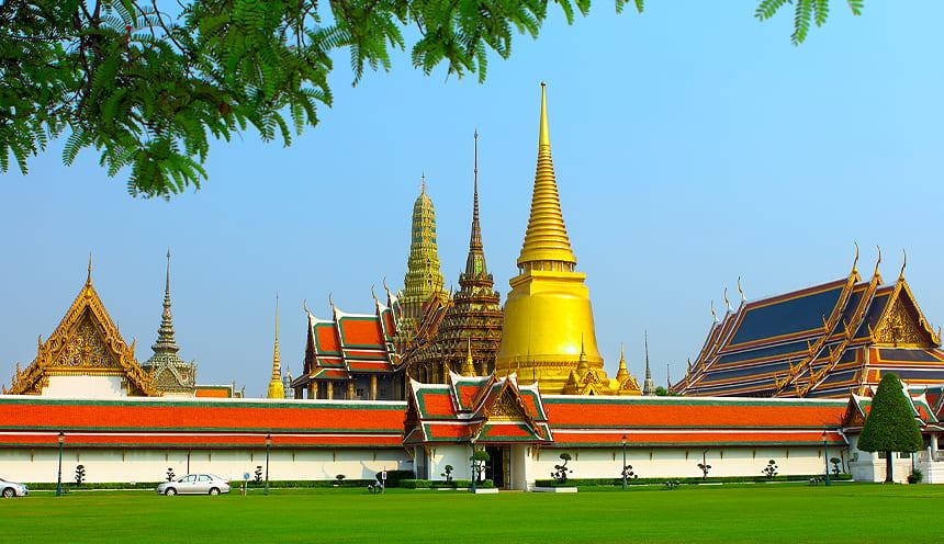 Vista di un muro bianco con tettoia arancione e dietro alte pagode doerate.