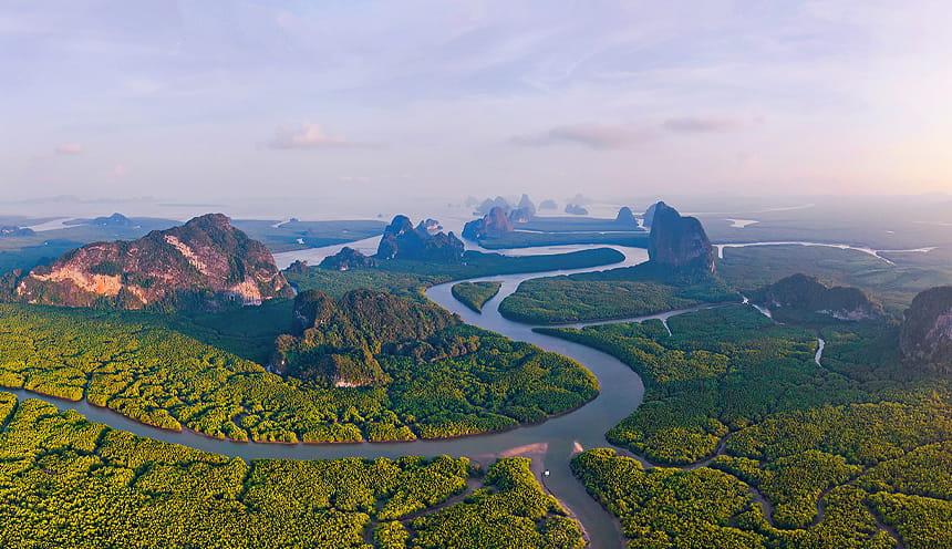 Un lungo e sinuoso corso d'acqua si snoda tra basse foreste di mangrovie e alcune formazioni rocciose sullo sfondo dove si trova una baia.