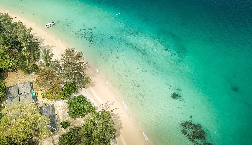 Vista aerea di una spiaggia sulla sinistra che entra in un mare smeraldo con fondo basso.