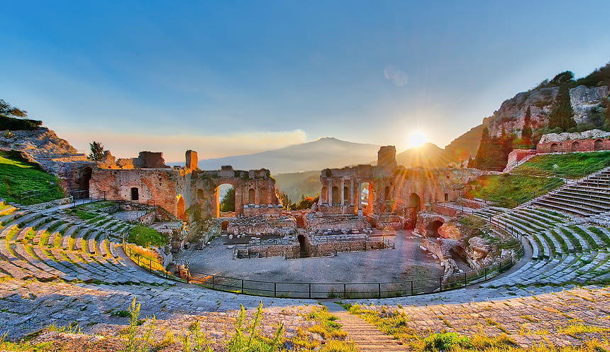 Panoramica di un teatro greco a con il tramonto alle spalle dei resti del palco.