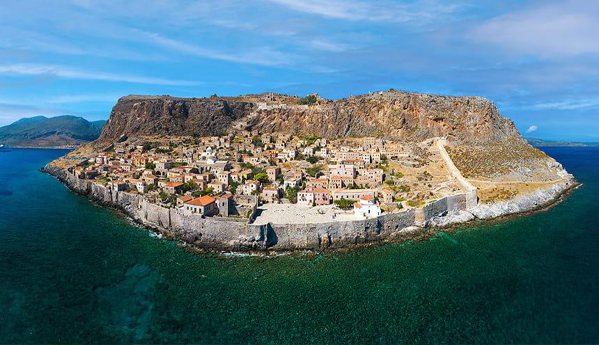 vista panoramica di una penisola rocciosa con arroccato un piccolo centro abitato circondato da mura