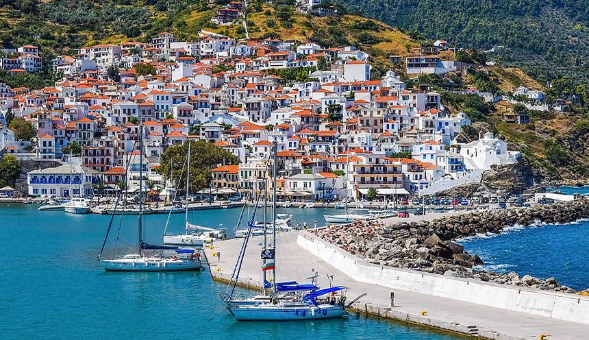 Scorcio della cittadina di Skopelos con diverse case bianche dal tetto arancio si inerpicano su la prete di una collina.