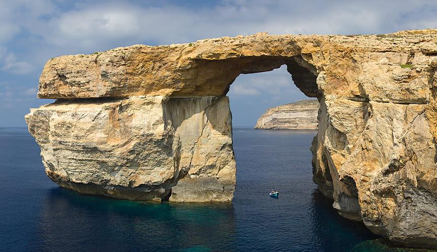scogliera che forma un arco naturale sul mare.