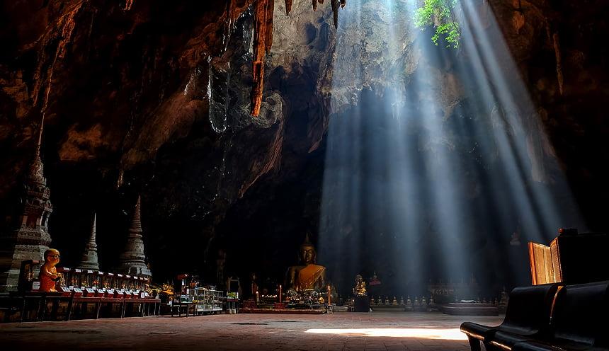 Una caverna alta con raggi di sole che filtrano e diverse statue del Buddha.