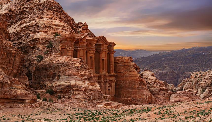 La facciata di un tempio scolpito sulla parete di una roccia nel deserto.