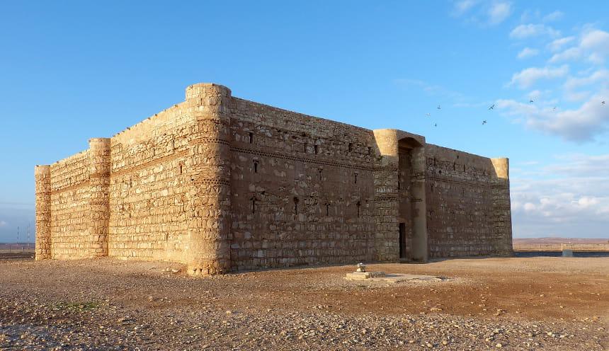 Un castello squadrato di mattoni in mezzo al deserto.