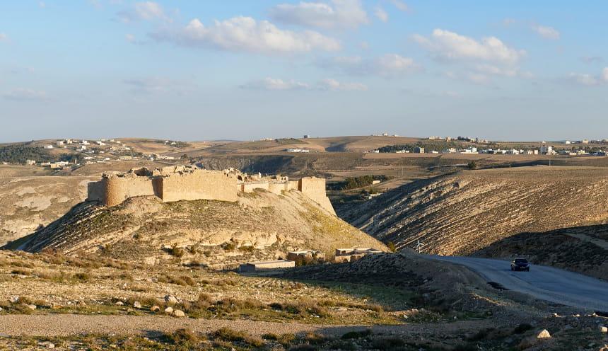 Alcune colline semi-desertiche con un castello sulla sommità di una.