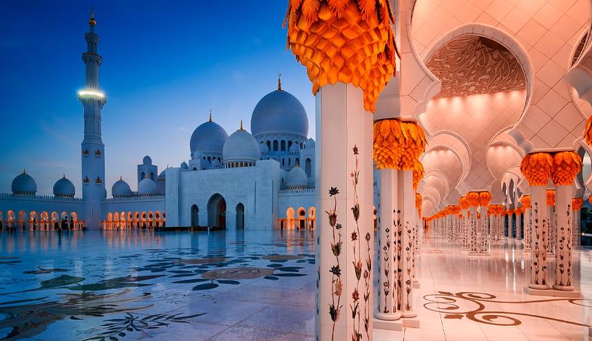 La sagoma blu di una moschea di sera e un corridoio illuminato sulla destra.