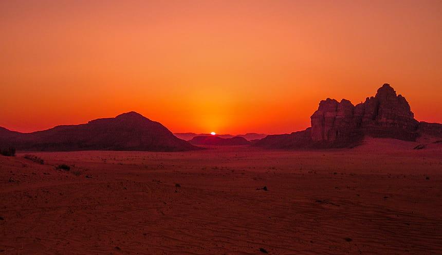 Il tramonto in un deserto con alcune alture rocciose.