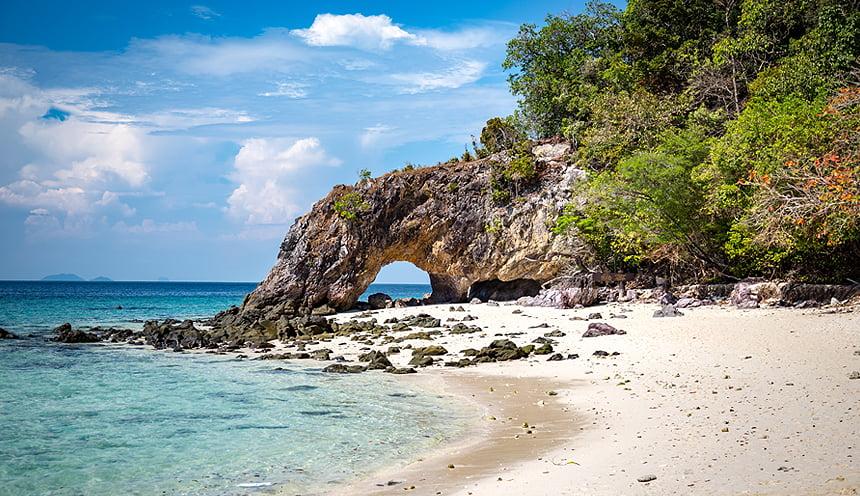 Una roccia a forma di arco finisce in un mare di acqua cristallina.