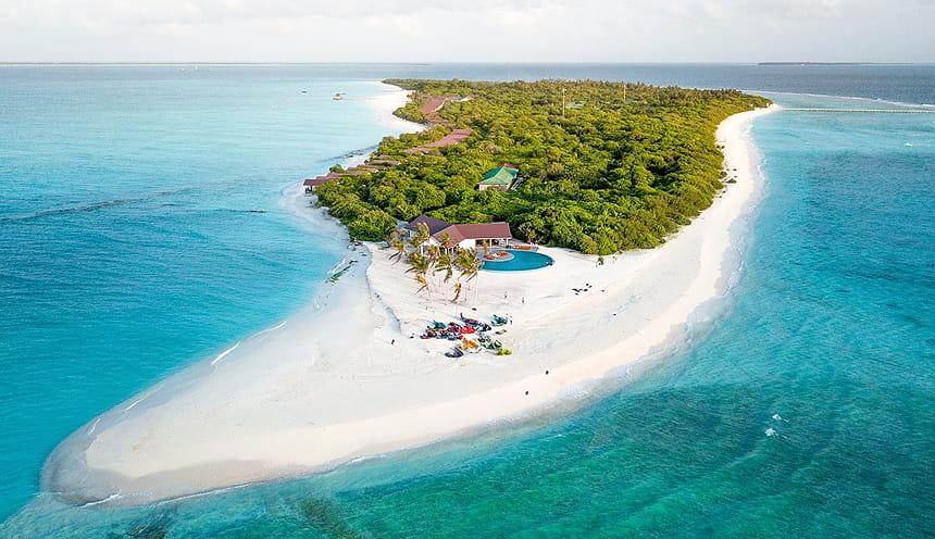 La punta sabbiosa di un atollo con alcune moto d'acqua parcheggiate sopra.