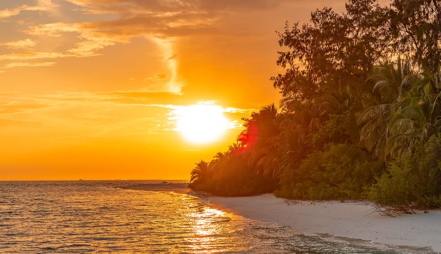 Tramonto arancio dietro alcune piante e alberi di un atollo.